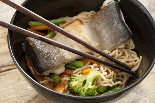 Asian noodles with fish fillet and vegetables