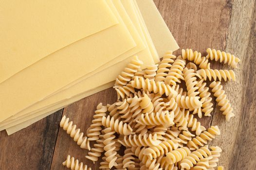 Lasagne with fusilli pasta on wooden background