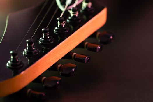 Closeup tuning key on the headstock of the black electric guitar in dark background and morning light. Copy space on the right. Concept of good memory About retro musical instruments and rock music.