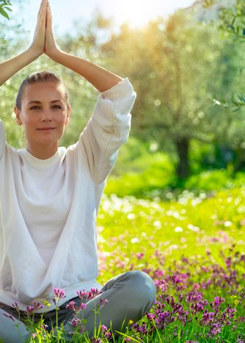 Beautiful woman doing yoga exercise outdoors, nice female in lotus pose meditating in beautiful fresh blooming spring garden, healthy lifestyle, relaxation and wellness concept