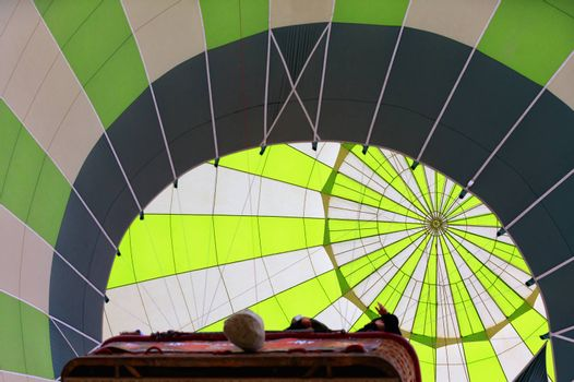Radial grooves in the center of a bright dome of a white-green balloon that lifts people in a wicker basket.