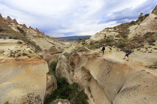 A young couple of tourists inspects a deep gorge standing on the edge of a canyon in Cappadocia against the background of a cloudy sky and mountain landscape.