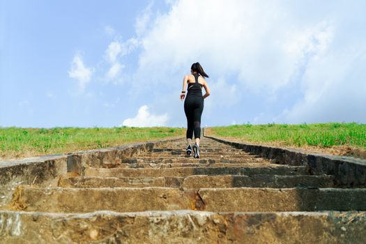young sport woman running outdoor upstairs on blue sky