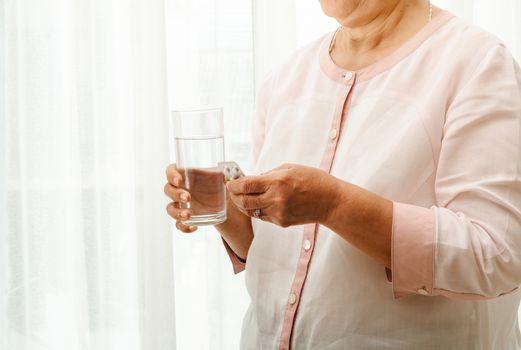senior women take medicine with a glass of water, healthcare and