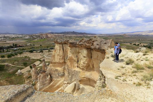 A young couple of tourists with backpacks on their backs stands on the edge of a cliff in Cappadocia and admires the surrounding space against the background of a blue stormy sky and mountain scenery.