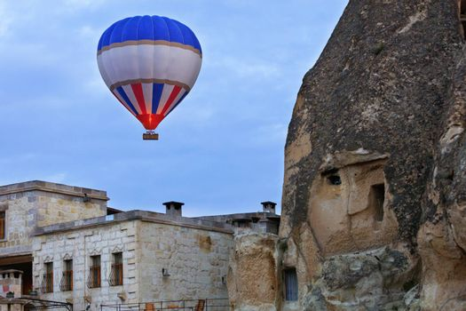 The flame of fire heats the air in a motley red-blue with a white beautiful balloon and raises a basket with tourists over the old city to the blue sky