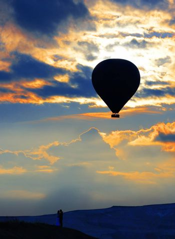 Silhouette of a couple in love on the horizon and a balloon against the background of the morning sky and fiery red clouds