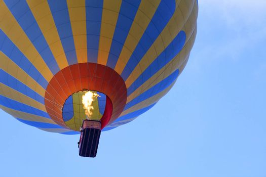 The flame of fire heats the air in a motley yellow-blue beautiful balloon and raises a basket of tourists to the blue sky, view from below.