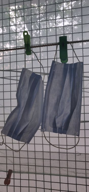 Two surgical mask hanging by clothes pin near a grilled window in a vertical photo during lock down in India