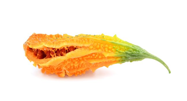 Ripe bitter melon with orange flesh, splitting open to show sticky red seeds, isolated on a white background