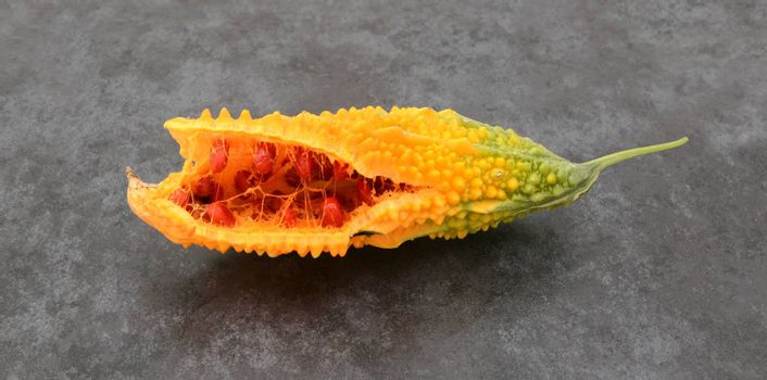 Orange bitter gourd, with ridged flesh, split open to show red seeds, on slate gray background