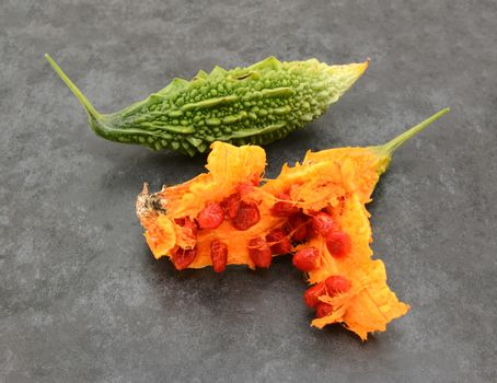 Green, ridged bitter gourd and an overripe orange fruit, split apart to show sticky red seeds - on a slate grey background