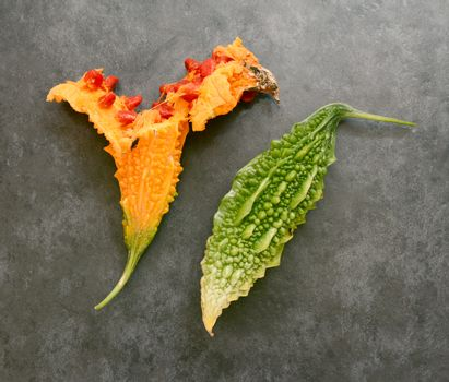 Orange, overripe bitter gourd split open with red, sticky seeds and a whole green bitter melon - on a slate gray background