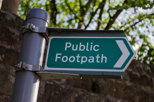 A clean and clear metal signpost giving the direction of a public footpath.