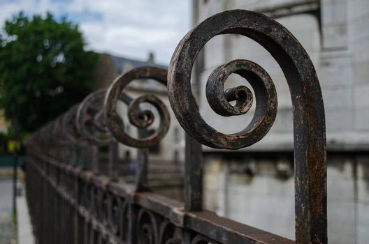 Retro scrolled metallic railings with a weathered appearance and a shallow depth of field