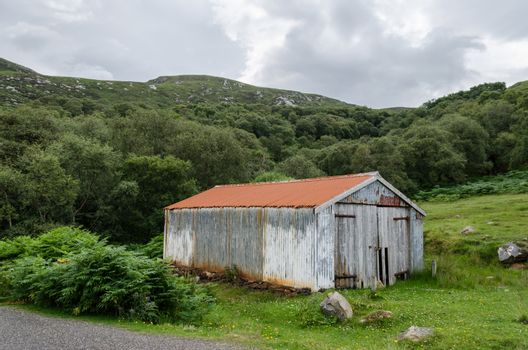 A delapidated and old corrugated garage or barn in a rural setting.