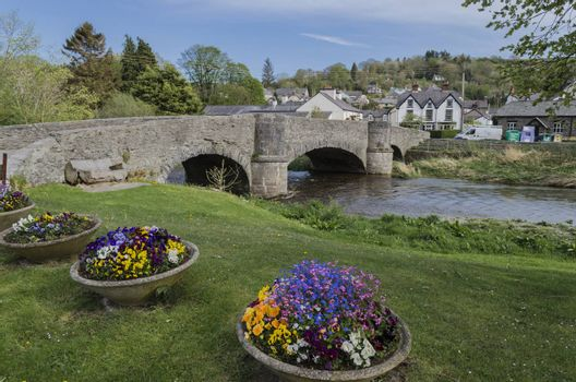 Pretty floral displays in forn of stone bridge in Welsh village