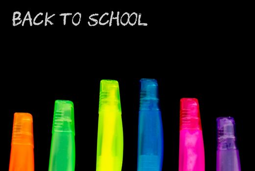 Back to school with colourful highlighter pens on a black bakground with copy space