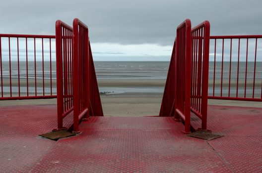 Rustic red railings leading to the sea