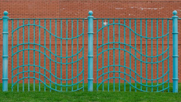 Aqua blue wavy fence built on grassed area with red brick wall behind