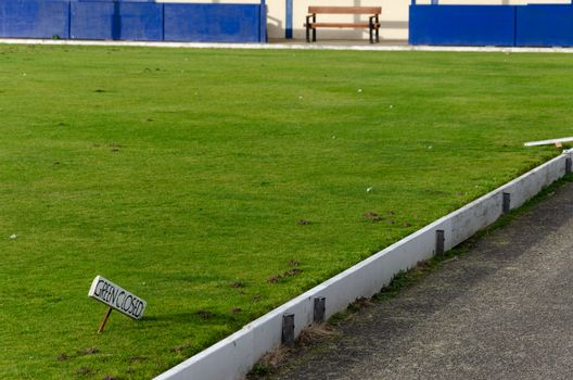 A small sign stating that the green is closed at a bowling green which is  in very poor condition in the seaside resort of Rhyl, North Wales