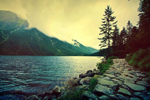Lake in mountains. Fantasy and colorfull nature landscape. Retro vintage picture.