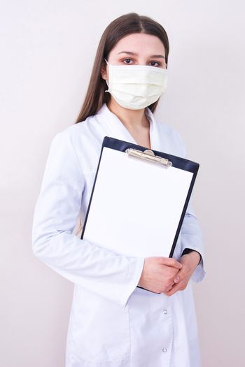 Female doctor wearing protection face mask holding notes. Free copy space. Covid-19 concept.