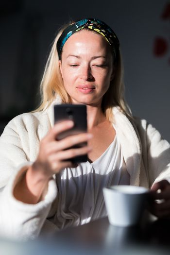 Beautiful caucasian woman at home, feeling comfortable wearing white bathrobe, taking some time to herself, drinking morning coffee and reading news on mobile phone device in the morning.