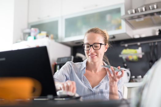 Stay at home and social distancing. Woman in her casual home clothing working remotly from kitchen dining table. Video chatting using social media with friend, family, business clients or partners.