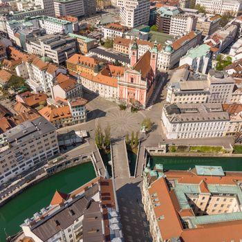 Aerial drone view of Preseren Squere and Triple Bridge over Ljubljanica river,Tromostovje, Ljubljana, Slovenia. Empty streets during corona virus pandemic social distancing measures.