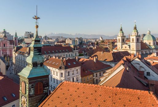 Scenic panoramic aerial drone view of rooftops of medieval city center, town hall and cathedral church in Ljubljana, capital of Slovenia, at sunset.