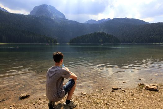 A teenager sits in the early morning on the shore of a mountain lake with a bottle of water and looks at the surface of the water.