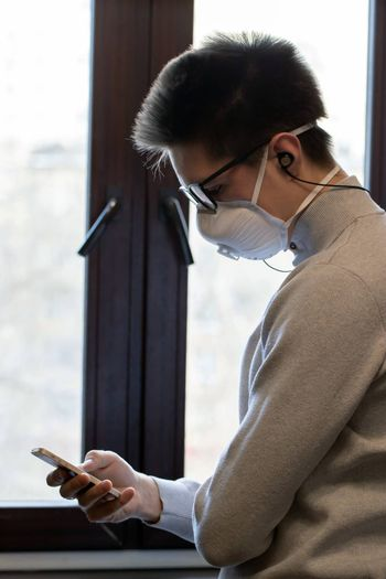 A young man in a reusable medical mask looks at the phone screen and reads messages from friends. Communication during a pandemic.