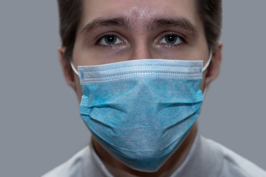 Young man in a medical mask smiles, portrait, close up, health care concept