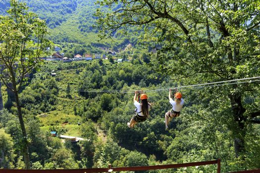 Girls on the cable car are sent through the mountain and the forest through the valley of the river Tiara in Montenegro.