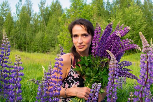 A beautiful woman with a large flower bouquet rests on a blooming field of lupins on a Sunny summer day