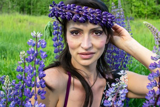 A beautiful woman with a flower wreath on her head rests on a blooming field of lupines on a Sunny summer day