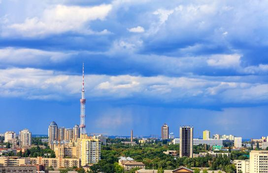 Cityscape of the summer city of Kyiv with a television tower and residential quarters in the impending thunderclouds on the horizon.