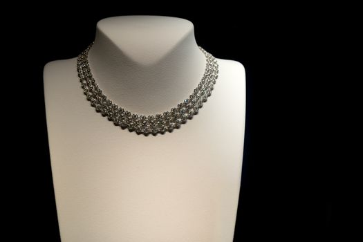 Female beautiful necklace on mannequin. Showcase jewelry store.