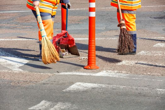 A janitor in a bright orange uniform sweeps the street and removes trash on the roadway and near the fence from the orange road columns.