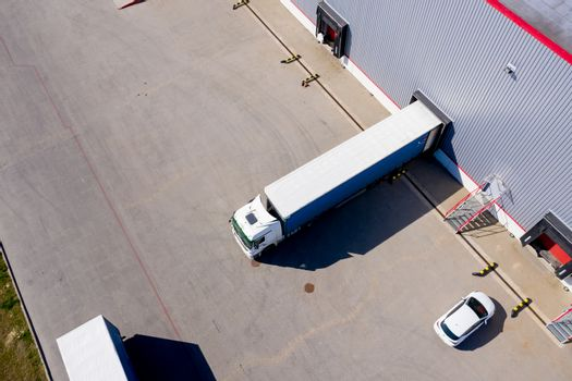 Aerial Side Shot of Industrial Warehouse Loading Dock where Many Truck with Semi Trailers Load/ Unload Merchandise
