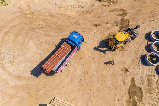 Industrial truck loader excavator moving earth and unloading. Aerial view