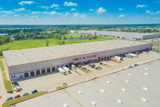 Aerial Shot of Industrial Warehouse Area where Many Trucks Are Loading Merchandise.