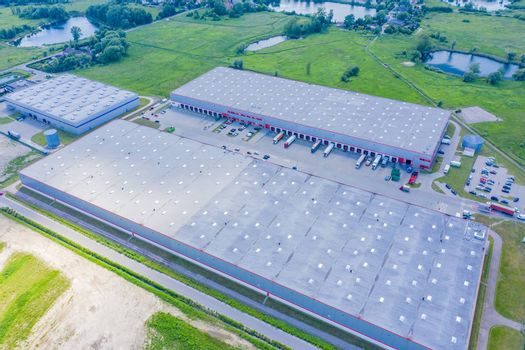 Aerial view of goods warehouse. Logistics center in industrial city zone from above. Aerial view of trucks loading at logistic center. View from drone