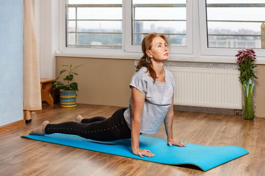 Beautiful middle-aged woman doing snake asana at home in her apartment, daily fitness exercises for muscle strain.