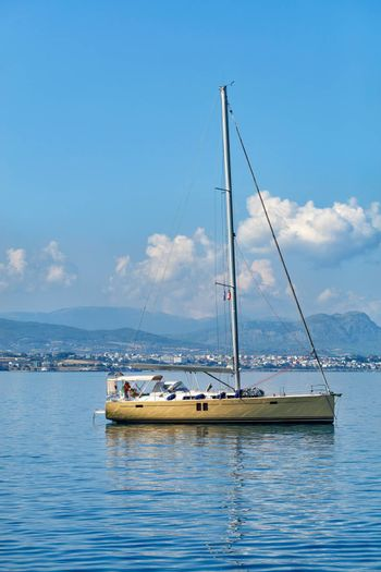 A sailing yacht is anchored against the backdrop of a mountain range and blue in the morning haze of the Gulf of Corinth and with small clouds in the blue sky.