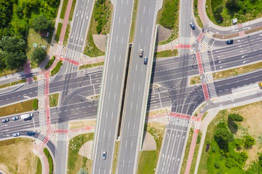 Traffic trails on highway intersection. Aerial View. Green Forest
