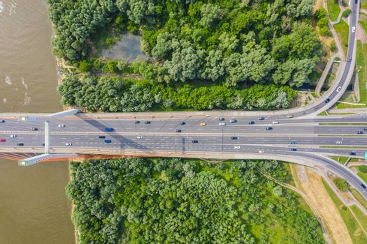 Car driving on highway bridge and road intersection in modern city aerial view