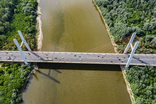 Aerial shooting from flying drone car traffic on modern highway bridge over river