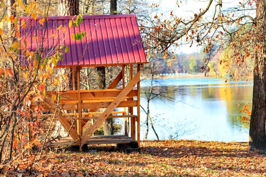 A simple wooden gazebo with a table and picnic benches, with a red roof made of metal siding, outdoors against a background of fallen leaves near a forest lake on a warm autumn day, copy space.